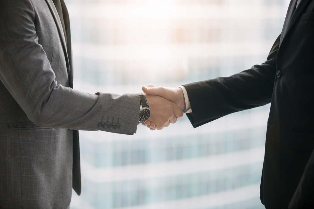 orelabrutinib | Multiple Sclerosis News Today | potential therapies | Close-up of hands of two business partners making deal