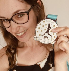 Image shows a young woman hoding up a medal showing 10 miles looking acomplished